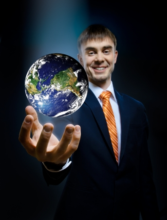 dominion: businessman hold in hand terrestrial globe, on dark blue background,  business concept image planet by: Stokli, Nelson, Hasler Laboratory for Atmospheres Goddard Space Flight Center www.rsd.gsfc.nasa.govrsd