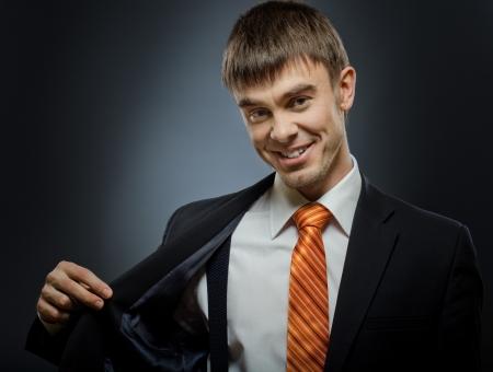 affability: portrait  the  beautiful  happy businessman in black costume and orange necktie,  smile Stock Photo