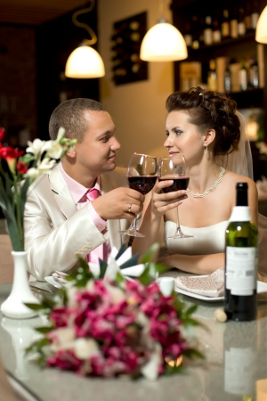 merriment: newly married couple sit at table in restaurant with  glass wine,  romance wedding dinner