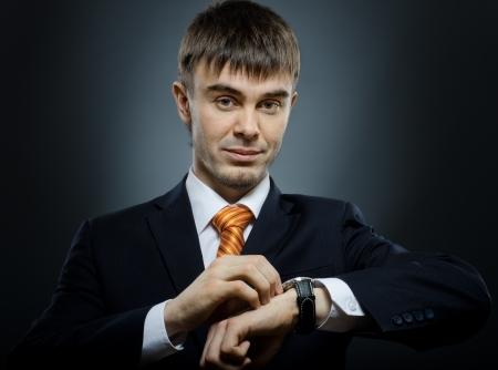 punctual: joven hombre de negocios en traje negro reloj de viento (reloj) en la mano