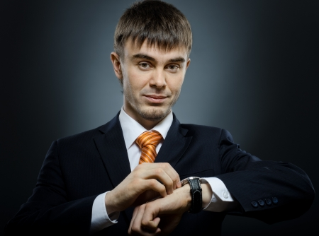 punctual: young businessman in black costume wind clock (wristwatch) on hand