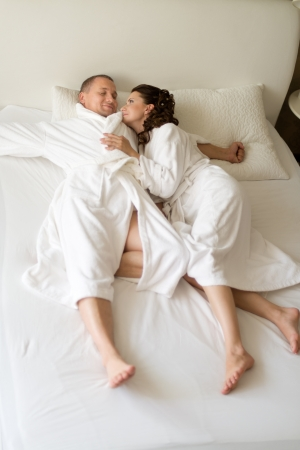 bedchamber: happy couple lie together in  bedstead on white bed,   sleep and embrace