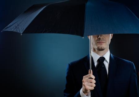 undercover: uomo ritratto l'uomo bello in costume blu con ombrello, l'agente speciale servizio Archivio Fotografico