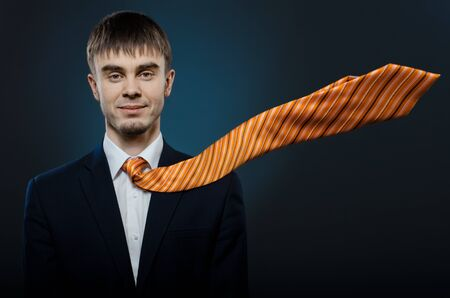 potentiality: portrait  the  happy beautiful  businessman careerist in costume and orange necktie