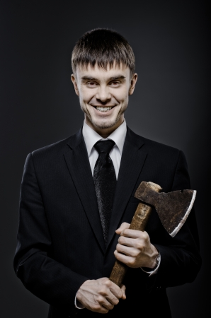 portrait  man  in black costume and black necktie with axe, sinister look and smile