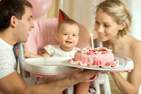 one-year-old little girl with daddy and mammy solemnize birthday, happy laughter, horizontal photo Stock Photo - 18205479
