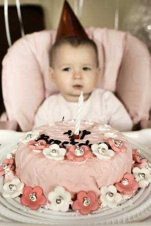 solemnize: one-year-old little girl solemnize birthday,melancholy mood, vertical photo