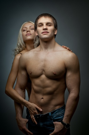 muscular handsome sexy guy with pretty woman, on dark background, glamour  light photo