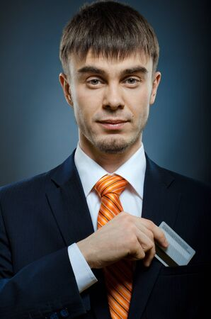 put up: businessman in black costume and orange necktie put or take out credit card in pocket Stock Photo