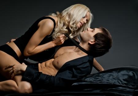 vrijen: gespierde knappe sexy man met mooie vrouw, op donkere achtergrond, glamour licht Stockfoto