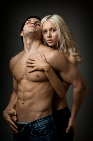 muscular body: muscular handsome sexy guy with pretty woman, on dark background, glamour  light