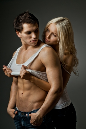 female sexuality: muscular handsome sexy guy with pretty woman, on dark background, glamour  light