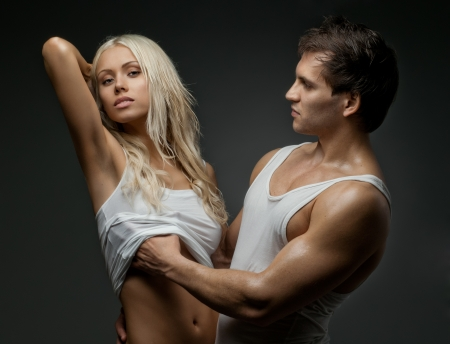 muscular handsome sexy guy with pretty woman, on dark background photo