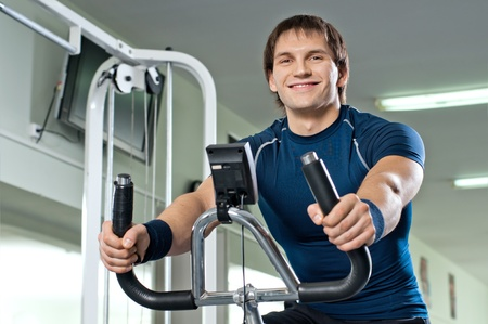 sports hall: beautifull strong athletic guy,  execute exercise on exercise-bicycle, in  sport-hall