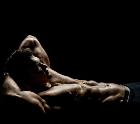 uomo nudo: il molto muscoloso ragazzo addormentato sexy, sdraiato su sfondo nero, il torso nudo Archivio Fotografico