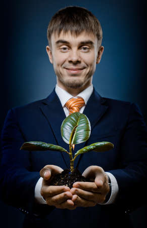 solicitous: vertical photo  businessman in blue costume with  scion  rubber plant Stock Photo