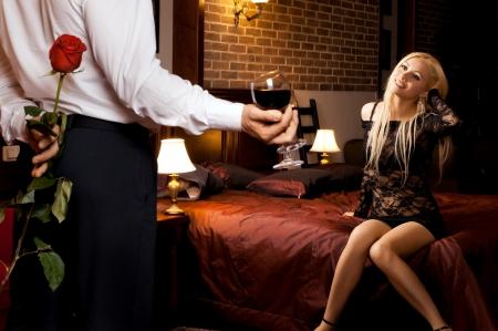 dattes: Date de soir�e romantique en chambre d'h�tel, mec avec fille sexy sur le lit Banque d'images