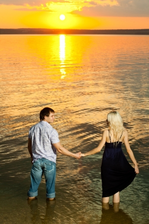 vertical photo the  happy  couple, outdoor on sunset or sunrise, in water  photo