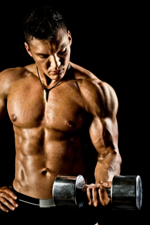 very power athletic guy ,  execute exercise with  dumbbells, on bkack background photo