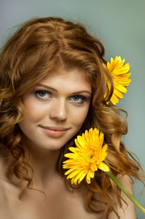 flower close up: the very  pretty red-haired blue eyed young woman  with yellow flower,  smile , vertical close up portrait