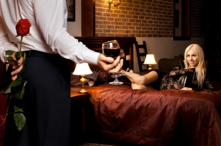 romantic evening date in hotel room, guy with  sexy girl on bed Stock Photo