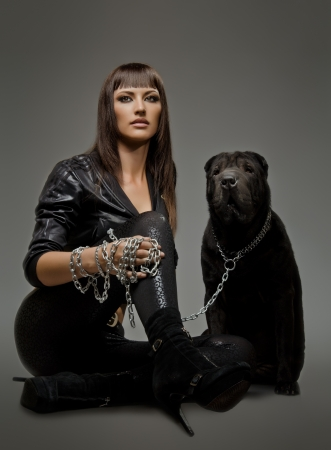 aegis: the beautiful  young woman sit with dog on grey background Stock Photo