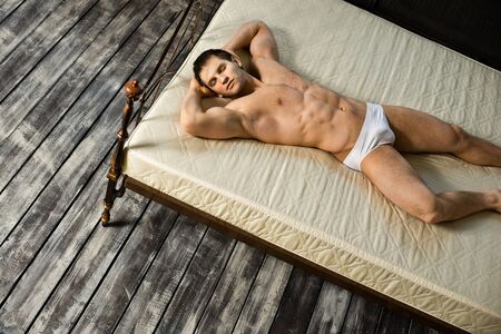 athletic type: the very muscular handsome sexy guy, sleeping  lie on bed,  in  bedroom
