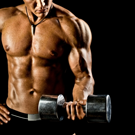 musculation: very power athletic guy ,  execute exercise with  dumbbells, on bkack background Stock Photo