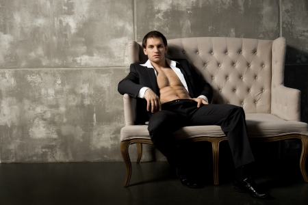 muscularity: the very muscular handsome sexy guy in black  suit indoor Stock Photo