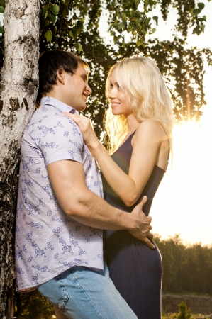 courting: romantic evening date on nature, couple  embrace on beautiful sunset   Stock Photo