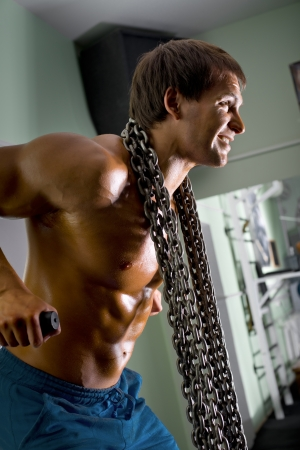 very power athletic guy  bodybuilder,  execute exercise on parallel bars, in sport hall Stock Photo - 20082596