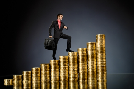 successfulness: businessman stand on top of  many rouleau gold  monetary  coin, on dark blue background Stock Photo