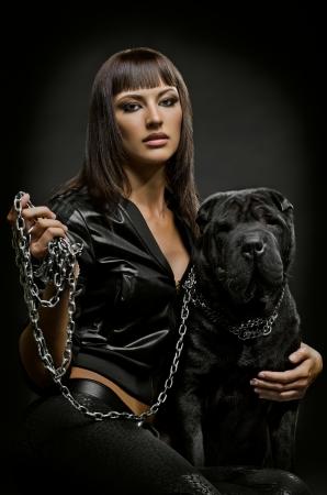 아름 다운 젊은 여자는 검은 색 바탕에 강아지와 함께 앉아 스톡 콘텐츠