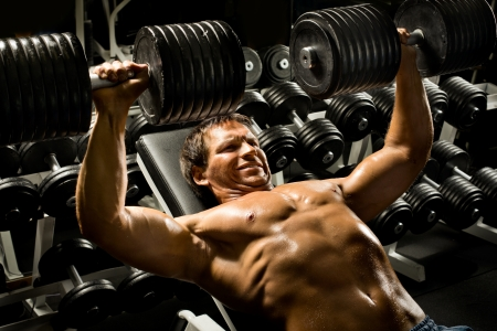 very power athletic guy ,  execute exercise press with  dumbbells, in sport hall Stock Photo - 20082588