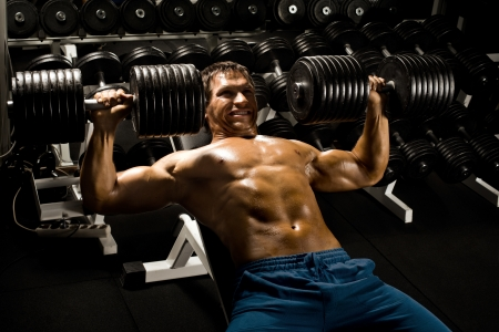 very power athletic guy ,  execute exercise press with  dumbbells, in sport hall Stock Photo - 20082554