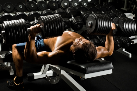 musculation: very power athletic guy ,  execute exercise press with  dumbbells, in sport hall
