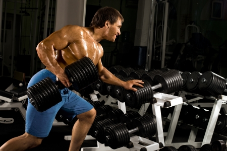 traction: very power athletic guy ,  execute  traction with  dumbbells, exercise on broadest muscle of back, in sport hall