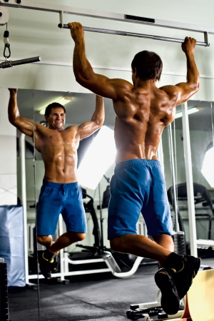 bodybuilder training: very power athletic guy ,  execute exercise tightening  on horizontal bar, in  sport-hall, glamour light Stock Photo