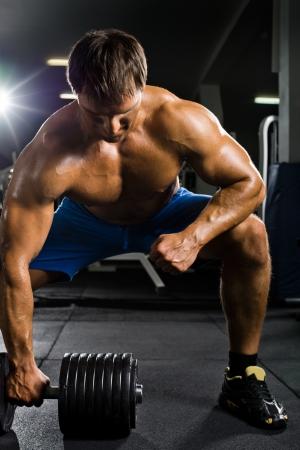 muskeltraining: sehr Macht athletische Kerl, f?hren Traktion mit Hanteln, ?ben am weitesten Muskulatur von R?cken, in der Sporthalle