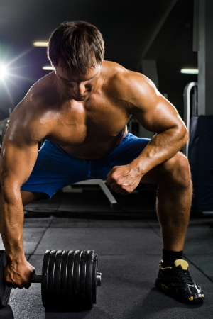 very power athletic guy ,  execute  traction with  dumbbells, exercise on broadest muscle of back, in sport hall Stock Photo - 20082593