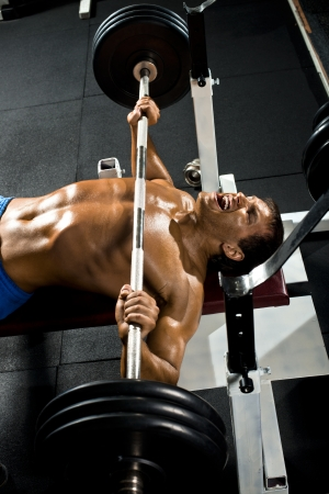 musculation: very power athletic guy ,  execute exercise press with weight, in sport hall