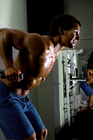 musculation: very power athletic guy ,  execute exercise on parallel bars, in sport hall