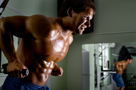 triceps: very power athletic guy ,  execute exercise on parallel bars, in sport hall