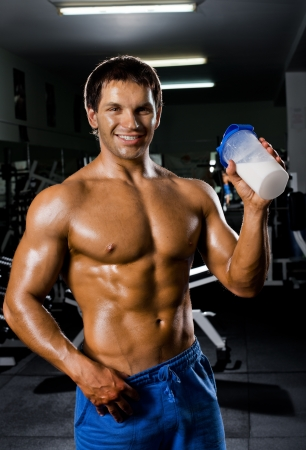 the very muscular sporty  guy drinking  protein in dark weight room