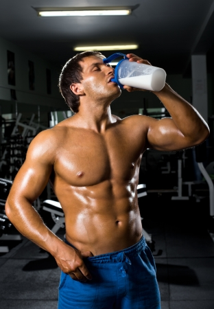 musculation: the very muscular sporty  guy drinking  protein in dark weight room,