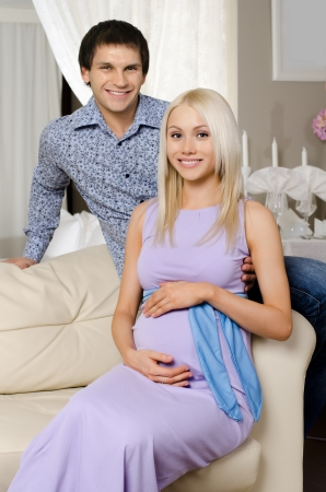 young fellow: young pregnant woman with husband  on white sofa in light  home room Stock Photo