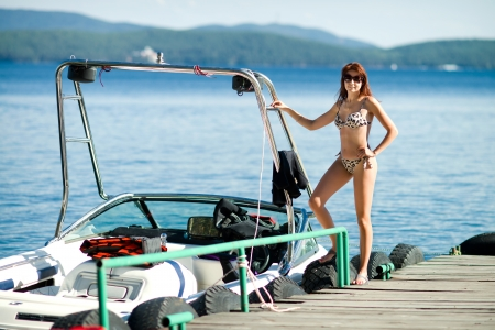 slender beautiful sexy girl, stand on  moorage  with  motorboat  on water background photo