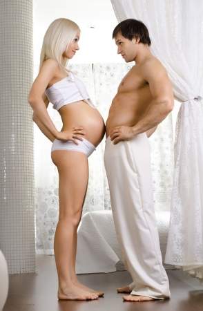 fetation: happy young pregnant woman with husband  in light  home room Stock Photo