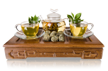 strew: still life of the glass teapot flow green tea in cup on wooden trivet, white background, isolated,  tea ceremony