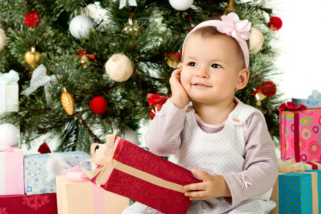 one-year-old little girl solemnize Christmas, sit under Christmas-tree with gift Stock Photo - 22307621